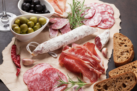 Salami, sliced ham, sausage, prosciutto, bacon, toasts, olives. Meat antipasto platter and red wine