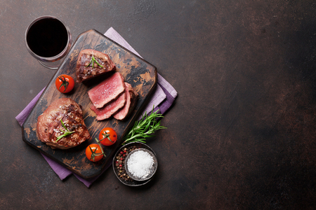 Grilled fillet steak with red wine on stone table. Top view with space for text