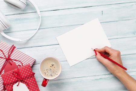 Vrouwelijke het schrijven groetkaart en verpakkende Kerstmisgiften. Bovenaanzicht met kopie ruimte Stockfoto