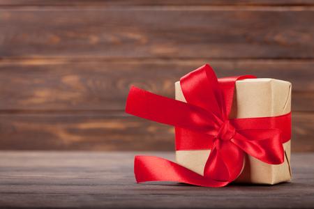 Contenitore di regalo di Natale davanti alla parete di legno con spazio per i saluti Archivio Fotografico - 89529754