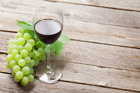 Wine glass and grapes on wooden table. With space for your text