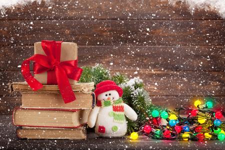 ギフト用の箱、雪だるまグッズ木製壁の前にカラフルなライトとクリスマスのグリーティング カード。あなたの挨拶のためのスペースと 写真素材