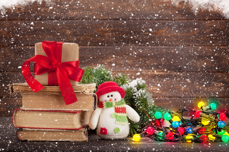 Christmas greeting card with gift box, snowman toy and colorful lights in front of wooden wall. With space for your greetings