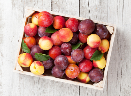 Fresh ripe peaches and plums in box on wooden table. Top view