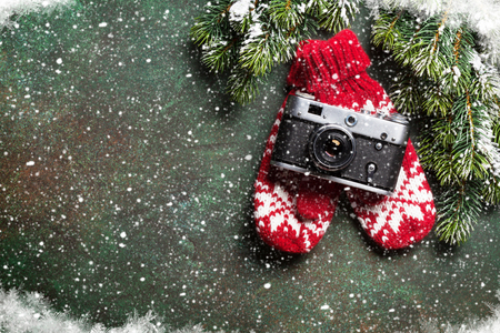 Xmas greeting card. Christmas background with snow fir tree, camera and mittens. View from above with space for your greetings or photo