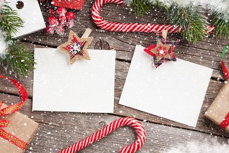 Kerstmis lege fotokaders, vogelhuisdecor en sneeuwspar op houten lijst. Bovenaanzicht met ruimte voor uw groeten