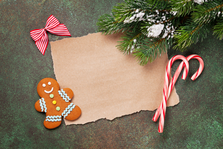 Piece of paper for christmas wishes, gingerbread man and snow xmas tree. Top view with space for text