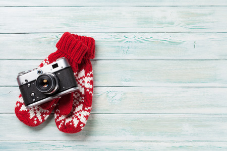 Xmas greeting card. Christmas background with camera and mittens. View from above with space for greetings or photo
