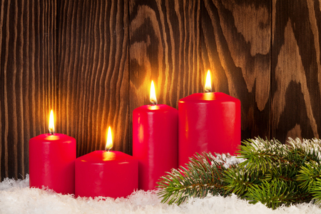 Christmas candles and snow fir tree in front of wooden wall with copy space