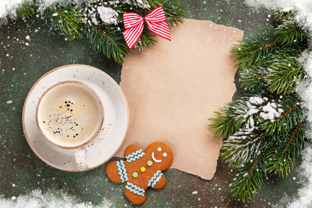 Piece of paper for christmas wishes, coffee cup and snow xmas tree. Top view with space for text