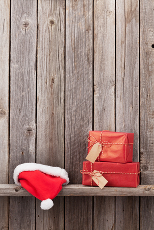 Christmas gift boxes and santa hat in front of wooden wall. View with copy space Stock Photo