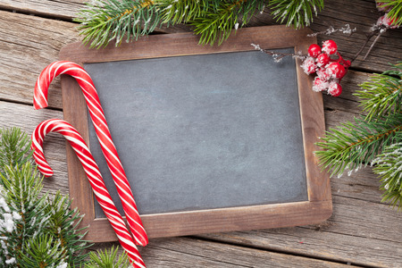 Christmas candy cane and snow fir tree on wooden table. Top view with chalkboard for your greetings Stock Photo