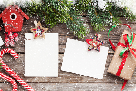 Christmas blank photo frames, birdhouse decor and snow fir tree on wooden table. Top view with space for your greetings Stock Photo