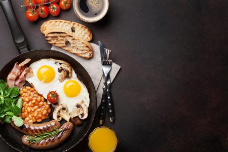 Englisches Frühstück. Spiegeleier, Würste, Speck, Bohnen, Toast, Tomaten, Orangensaft und Kaffeetasse auf Steintabelle. Draufsicht mit Kopienraum Standard-Bild - 90800506