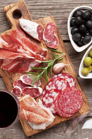 Salami, jambon en tranches, saucisse, prosciutto, bacon, toasts, olives. Plateau d'antipasti à la viande et vin rouge sur une table en bois. Vue de dessus Banque d'images - 90800520