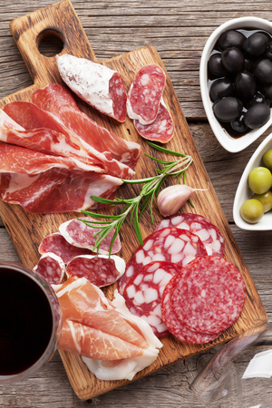 Salami, sliced ham, sausage, prosciutto, bacon, toasts, olives. Meat antipasto platter and red wine on wooden table. Top view Stock Photo