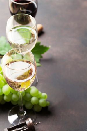 Wine glasses and grapes on stone table. With space for your text
