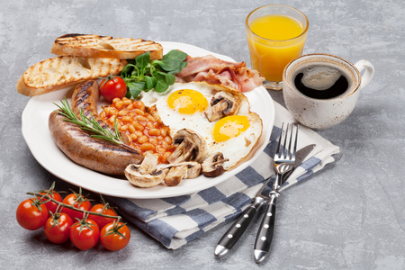 English breakfast. Fried eggs, sausages, bacon, beans, toasts, tomatoes, orange juice and coffee cup Stock Photo