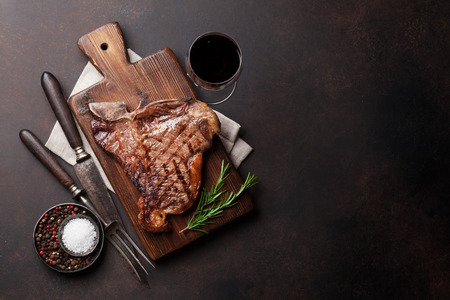 Grilled T-bone steak and red wine glass on stone table. Top view with copy space