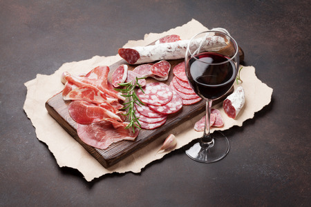 살라미 소시지, 슬라이스 햄, 소시지, 햄, 베이컨 및 레드 와인 글라스. 돌 테이블에 고기 전채 플래터 스톡 콘텐츠