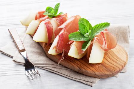 生ハムとミントの新鮮なメロン。前菜。木製のテーブルの上