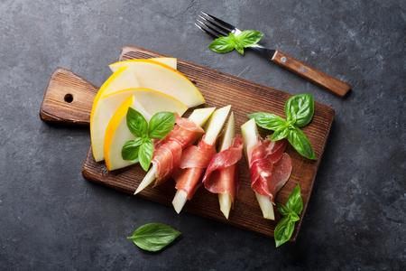 生ハムとバジルのフレッシュメロン。前菜。暗い石のテーブルの上のビュー