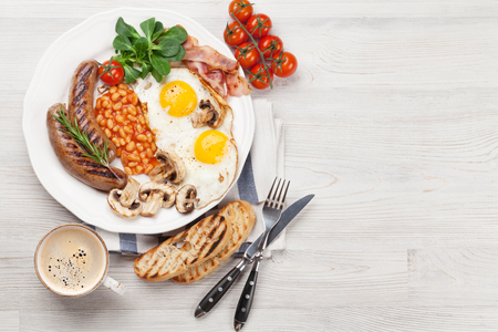 Englisches Frühstück. Spiegeleier, Würste, Speck, Bohnen, Toast, Tomaten und Kaffeetasse auf Holztisch. Draufsicht mit Kopienraum Standard-Bild - 91711398