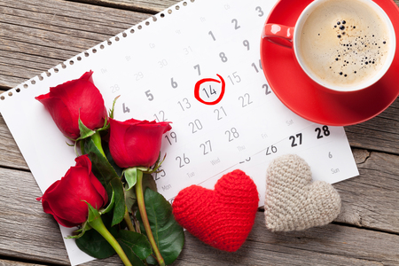 Valentines day greeting card. Red rose flowers, coffee cup and heart toys over february calendar on wooden table. Top view Stock Photo
