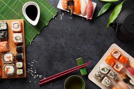 Set sushi en maki roll en groene thee op stenen tafel. Bovenaanzicht met kopie ruimte