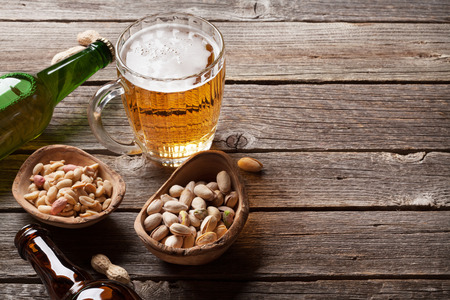 Lager beer and snacks on wooden table. Various nuts. With copy space