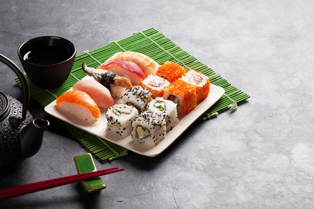 Set of sushi, maki and green tea on stone table. View with copy space