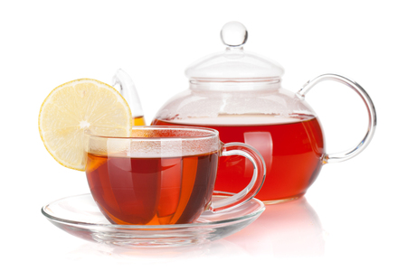 Glass teapot and cup of black tea with lemon slice. Isolated on white background