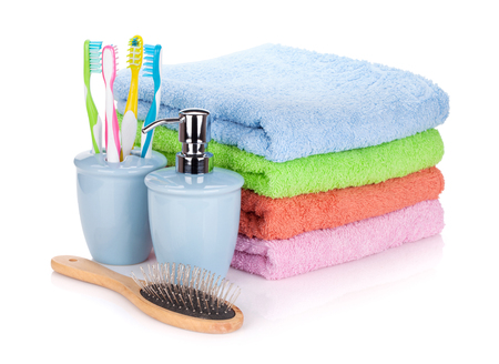 Four toothbrushes, liquid soap, hairbrush and colorful towels. Isolated on white background