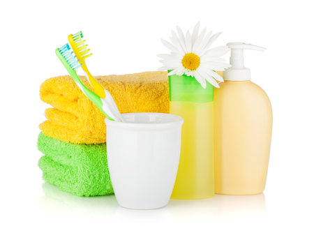 Toothbrushes, shampoo bottles, two towels and flower. Isolated on white background