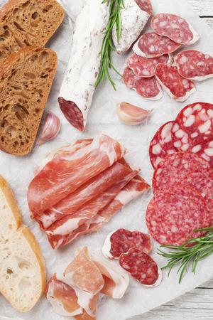 Salami, lonchas de jamón, chorizo, jamón, tocino, tostadas, aceitunas. Antipasto de carne. Vista superior