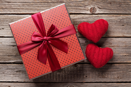 Valentines day greeting card with gift box and red hearts on wooden table. Top view