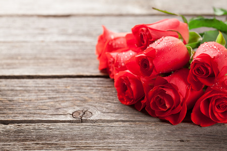 Valentines day greeting card with red rose flowers on wooden table. With copy space for your text