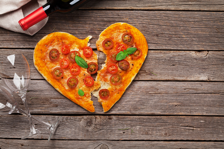 Heart shaped pizza with tomatoes and mozzarella and red wine. Valentines day greeting card. Top view with space for your text