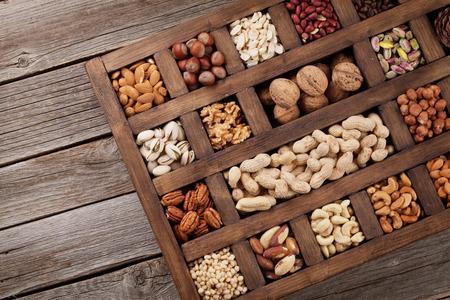 Verschiedene Nüsse Auswahl: Erdnüsse, Haselnüsse, Kastanien, Walnüsse, Pistazien und Pekannüsse in Holzkiste. Draufsicht mit Platz für Ihren Text