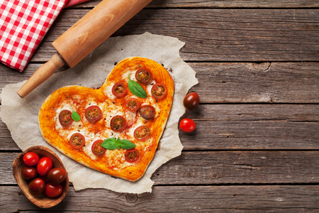 Heart shaped pizza with tomatoes and mozzarella. Valentines day greeting card. Top view with space for your text