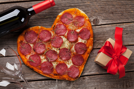 Heart shaped pizza with pepperoni and mozzarella and red wine bottle. Valentines day greeting card. Top view