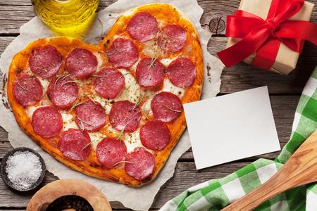 Pizza a forma di cuore con peperoni e mozzarella. Biglietto di auguri di San Valentino. Vista dall'alto con spazio per il testo Archivio Fotografico - 92981896