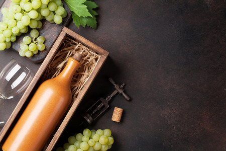 Wine bottle and grapes on stone table. Top view with space for your text