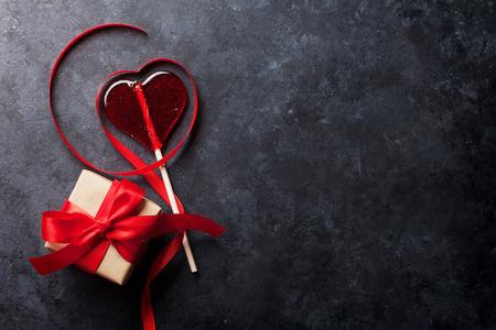 バレンタインデーのグリーティングカード。石のテーブルの上にキャンディハートとギフトボックス。コピースペース付きのトップビュー
