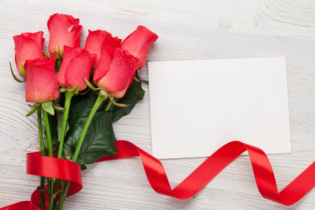 Valentines day greeting card with red roses on wooden background. Top view with space for your greetings