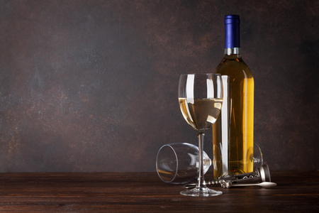 White wine bottle and glass in front of blackboard wall. With copy space for your text