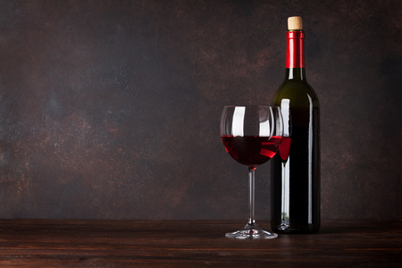 Red wine bottle and glass in front of blackboard wall. With copy space for your text Фото со стока
