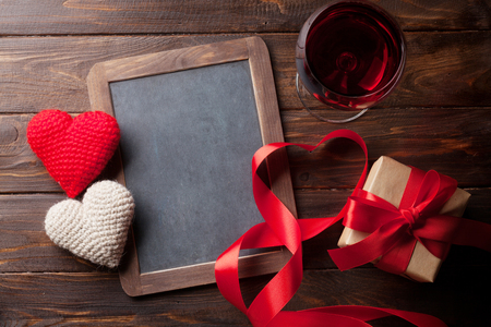 Valentines day greeting card with red wine, heart toys and gift box on wooden table. With chalkboard for your greetings