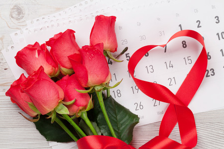 Valentines day greeting card with red roses and heart shaped ribbon over february calendar on wooden background. Top view