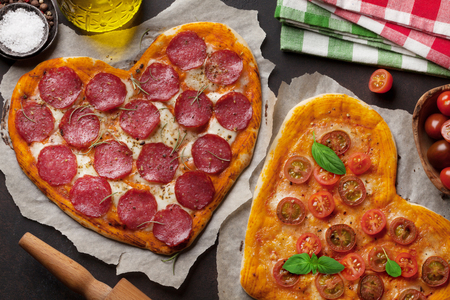 Heart shaped pizza with pepperoni, tomatoes and mozzarella. Valentines day greeting card. Top view